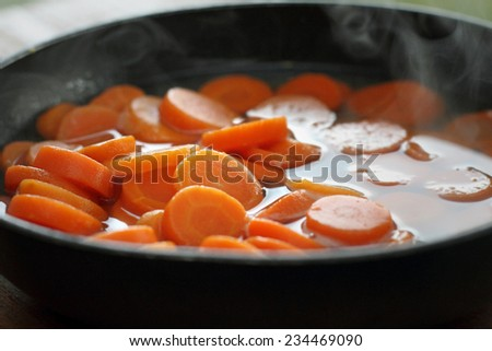 Hot steaming canned carrots in frying pan. - stock photo