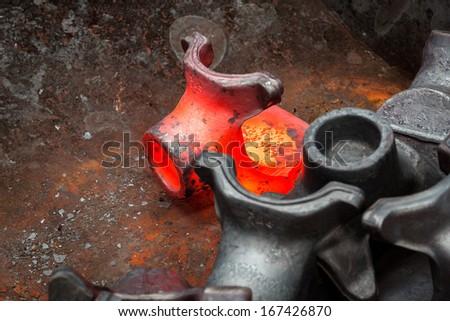 Hot steel ingot in the workspace - stock photo