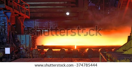 hot steel plate on conveyor in steel plant - stock photo