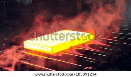hot steel sheet on conveyor; sheet metal - stock photo
