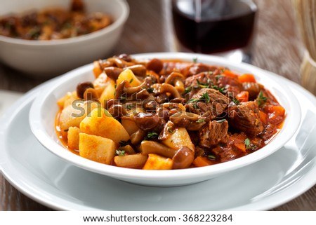 Hot stew with mushrooms and potatoes - stock photo