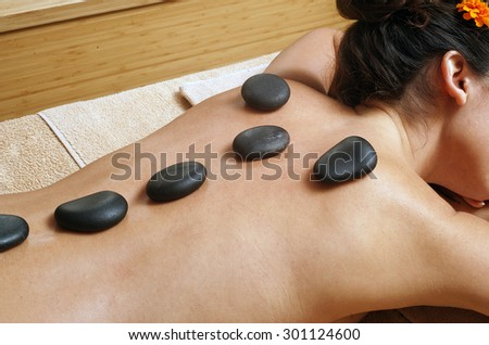 Hot stone massage in spa salon - stock photo