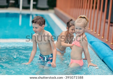 hot summer day little children playing in the azure pool