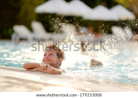 hot summer day, the boy fun dives and swims in the pool