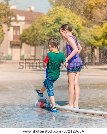 Hot summer in the city - girl and boy are enjoying fountain with cold water - stock photo