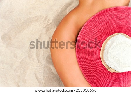 Hot summer tanned body. Naked woman body curves. Hips and waist covered with red straw summer hat. - stock photo