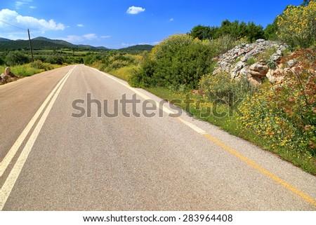 Hot sun illuminate straight road across Attica, Greece - stock photo