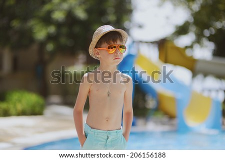hot sunny day a little boy standing at the pool with hat and sunglasses - stock photo