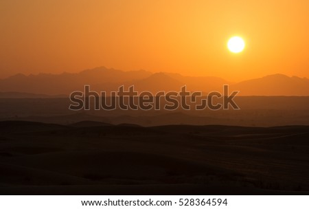 Hot sunrise in the desert dunes of Dubai, United Arab Emirates.