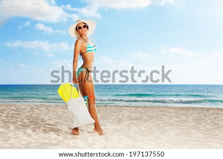 Hot tall girl with flippers in her bag  standing on white sand beach wearing blue striped swimwear - stock photo