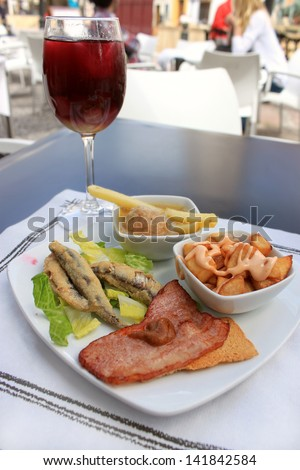 Hot tapas consisting of fried sardines, bacon on a tostada, fries with sauce and meatball, with a glass of sangria, food from Andalusia, Spain - stock photo