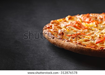 hot tasty delicious rustic homemade american pizza with pineapple chicken tomato with thick crust on black table - stock photo