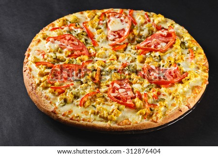 hot tasty delicious rustic homemade american pizza with tomato curry chicken  with thick crust on black table - stock photo