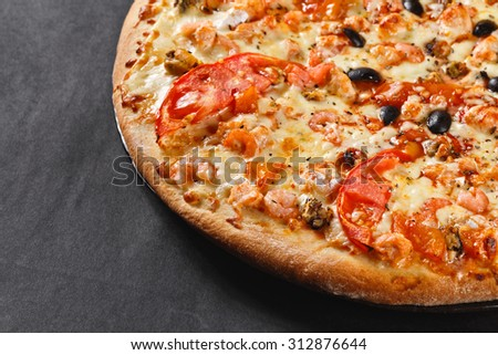 hot tasty delicious seafood homemade american pizza with shrimps with thick crust on black table - stock photo