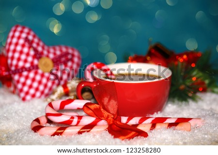 Hot tasty drink in red cup with Christmas candies on blue background - stock photo