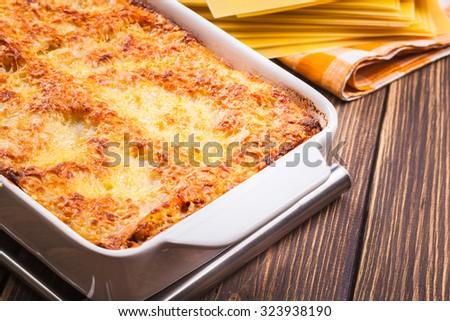 Hot tasty lasagna in ceramic casserole dish - stock photo