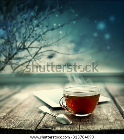 Hot tea cup on a frosty winter day window background/ Christmas holidays background/ Winter cozy background - stock photo