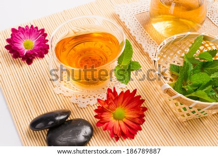 hot tea,flowers,mint on bamboo sticks mat