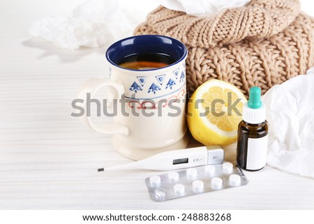 Hot tea for colds, pills and handkerchiefs on table close-up - stock photo
