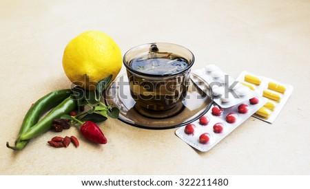 Hot tea for colds, pills and handkerchiefs on table,lemon and peppers, natural remedy   - stock photo