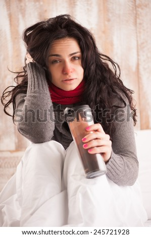 Hot tea healing. Closeup image of young sick woman with scarf on her neck sitting in bed with a big mug of tea in country house on the background - stock photo
