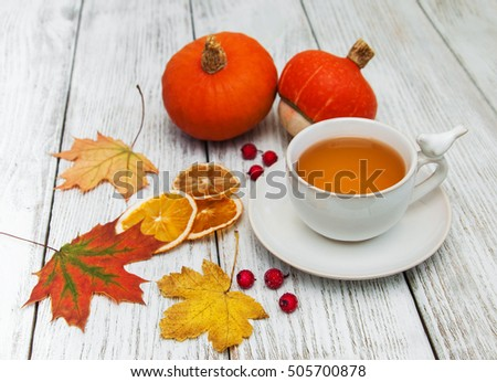 hot tea  in  cup and colorful  falling leaves