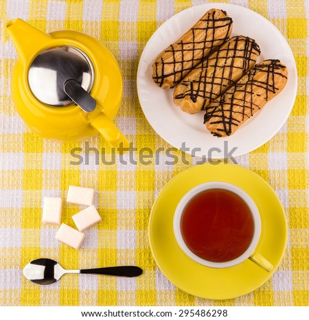 Hot tea in cup, sugar cubes and eclairs on yellow plaid tablecloth, top view - stock photo