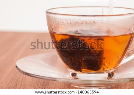 Hot tea in the making on a wooden table close up - stock photo