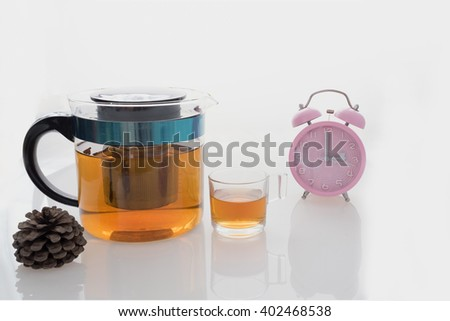 Hot tea set with glass cup and glass pot on isolated background with pink clock on tea time at 3 pm  / Hot tea set with glass cup and pot on isolated background at tea time - stock photo