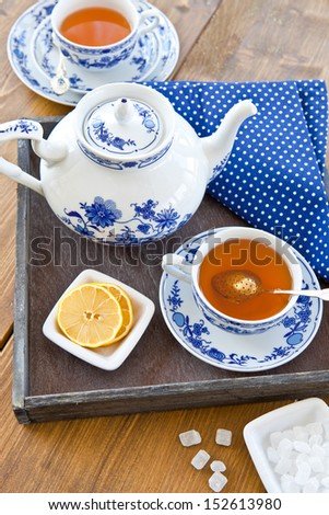 Hot tea with a slice of fresh lemon on a wooden tray - stock photo