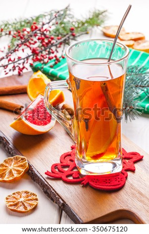 Hot tea with citrus, cinnamon, cloves and honey on a wooden table.