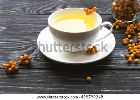 Hot tea with fresh sea buckthorn berries on black wooden background.