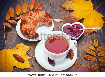 Hot tea with maple leaves and raspberry jam