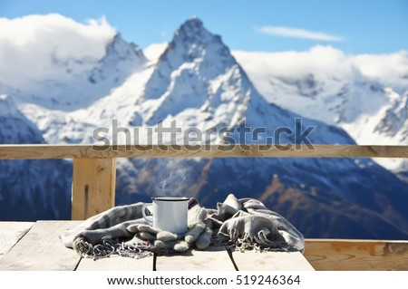 Hot tea with steam in tin mug, warm mittens and scarf on wooden table against snowy mountain peaks. Breakfast on terrace of cafe in mountain resort.