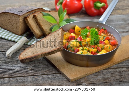 Hot vegetarian potato goulash served in an iron pan with delicious dark baked farmhouse bread on an old wooden table, a Tyrolean mountain specialty, a typical dish for hikers and mountaineers   - stock photo