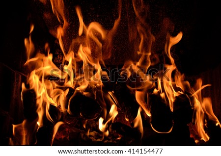 Hot vivid burning birch logs in fireplace on a cold winter day