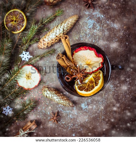 hot wine punch with dried fruit, cinnamon and anise on dark wooden table with christmas decoration and snow, top view, toned - stock photo