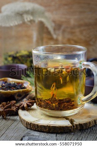 Hot winter tea with spices on wooden table.