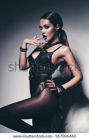 hot woman in black biting finger - stock photo