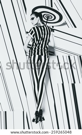 hot woman in striped top and leggings with spiral umbrella in studio - stock photo