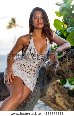 Hot woman posing on tree trunks over the outdoors background - stock photo