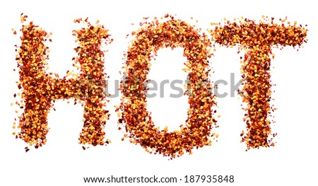 HOT written in dried crushed chilis on a white background - stock photo