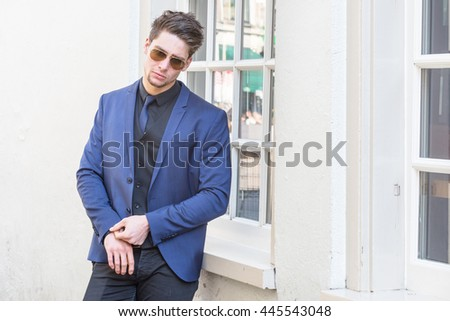 Hot young and cool macho male model. Attractive man relaxing and wearing a blue suit and tie and wearing sunglasses standing near a window - stock photo