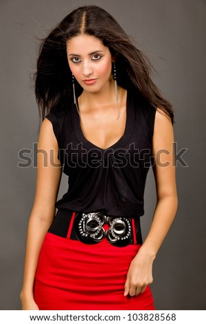 Hot young brunette in red skirt and black blouse against grey background - stock photo