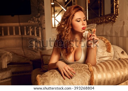 Hot young lady with big boobs drinks martini . Seductive woman. Sexual woman. the concept of seduction, pleasure and desire - stock photo