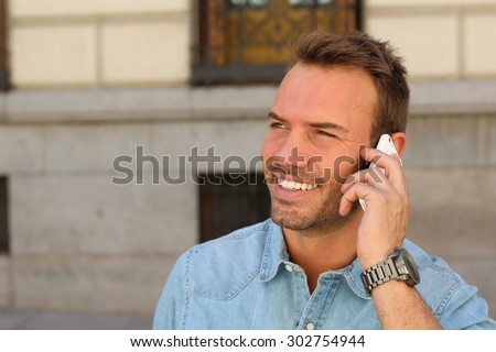 Hot young man calling with mobile phone . He is calling somebody by mobile telephone on the street