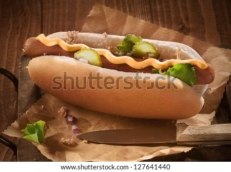 Hotdog bun with sausage with mustard and pickles - stock photo