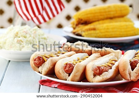 Hotdogs with Mustard, cole slaw and corn on a cob at a 4th of July BBQ picnic. Extreme shallow depth of field. - stock photo