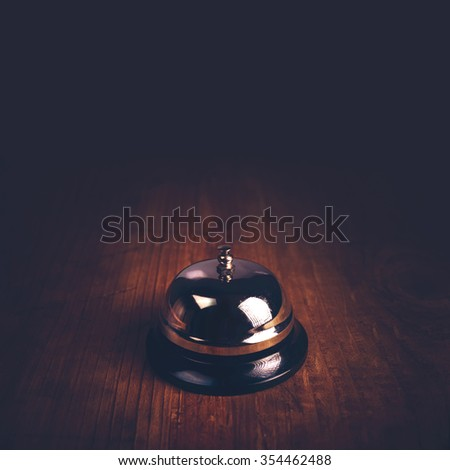 Hotel accommodation call bell on wooden reception front desk, retro toned image, selective focus - stock photo