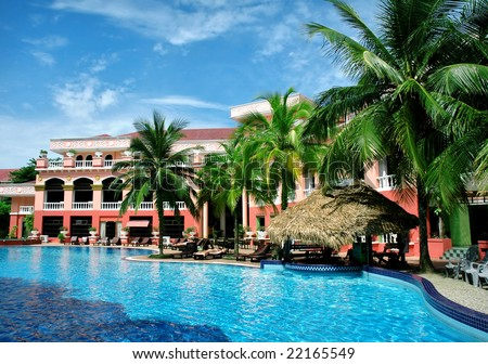 hotel and swimming pool with palm - stock photo